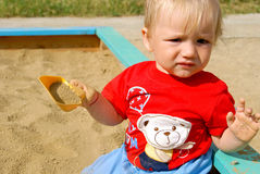 The kid in a sandbox. The child sits in a sandbox and holds a scoop in a hand Stock Image