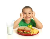 Kid with a sandwich meal. Six year old boy ready to eat a healthy lunch of sandwich on whole wheat bread, tortilla chips, apple, and milk Royalty Free Stock Photos