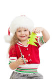 Kid in Santa Claus hat cutting christmas tree Royalty Free Stock Image