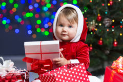Kid Santa Claus near Christmas tree with gifts Royalty Free Stock Photos