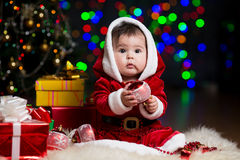 Kid Santa Claus near Christmas tree with gifts Stock Images