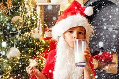 Kid Santa Claus takes a cookie on Christmas Eve as a thank you gift for leaving presents to a grateful boy or girl