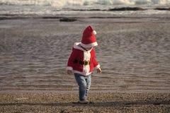 Kid in santa costume walking barefoot on sea beach stock image