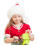 Kid in Santa hat cuts christmas tree from paper Stock Image