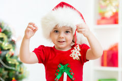 Kid in Santa hat holding Christmas cookies. Kid girl in Santa hat holding Christmas cookies stock photo