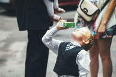 Kid Satisfaction. Boy Drinking Juice with Appetite on Wedding Event Royalty Free Stock Photos
