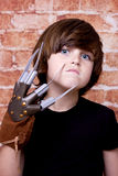 Kid with  scary nails on face. Brick wall Royalty Free Stock Images