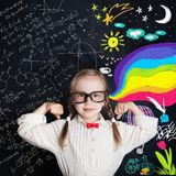 Kid of school age on arts and science background. Little girl student showing his power royalty free stock image
