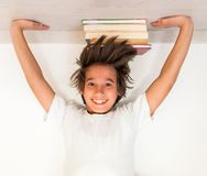 Kid with school books upside down Stock Photo