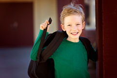 Kid at school. Excited smiling schoolboy with backpack enjoying time at school, back to school concept Royalty Free Stock Photography