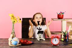 Kid and school supplies on pink background. Schoolgirl at desk. With yellow flowers, red clock, fruit and colorful stationery. Girl with surprised face uses royalty free stock photo