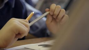 Kid in School. Teenager or kid writing notes with a pen in notebook lying at the desk. Kids in primary school. Handheld close up shot stock video footage