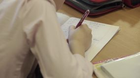 Kid at School. Teenager or kid writing notes with a pen in notebook lying at the desk. Kids in primary school. Handheld close up shot stock footage