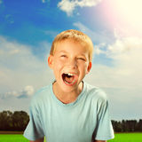 Kid screaming outdoor. Toned photo of the Happy Kid screaming outdoor Royalty Free Stock Photos
