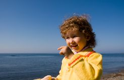 Kid and sea. The girl looks at the sea, in hands a soft toy Stock Photo
