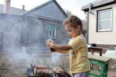 Kid seasoning pork chops with pepper Stock Photos