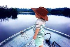 Kid at Serene Lake. Kid on fishing boat with cowboy hat watching serene lake view Royalty Free Stock Image