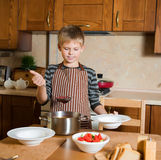 Kid serving Borshch, traditional Russian and Ukrainian soup. Pouring soup into a plate with ladle from pan in kitchen. Royalty Free Stock Photos