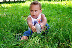 Kid shoe. Little boy sitting on the grass itself sandals shoes stock photo