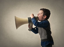 Kid shouting through loudspeaker. Boy holding a loudspeaker and screaming loud Stock Image