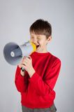Kid shouting in megaphone on bright background royalty free stock photo