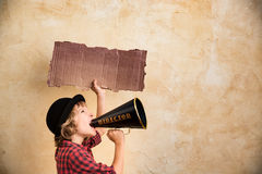 Kid shouting through megaphone. Kid shouting through vintage megaphone. Communication concept. Retro style Stock Photo