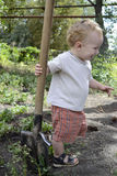 Kid with a shovel. One year old blond kid with a big shovel Stock Image