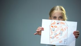 Kid showing house picture into camera, poor family needing home, social support. Stock photo royalty free stock photo