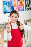 Kid showing thumb up and holding painting brush in workshop of. Art school royalty free stock photos
