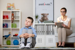 Kid sick of autism. Psychologist in glasses is looking at kid sick of autism sitting on carpet in classroom. Autistic child therapy concept Stock Photography