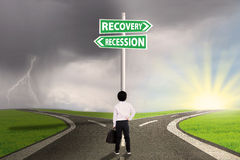 Kid with signpost directing to recession and recovery financial Royalty Free Stock Photos