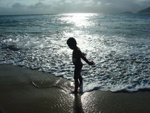 Kid in silhouette. Kid playing in the beach Stock Image