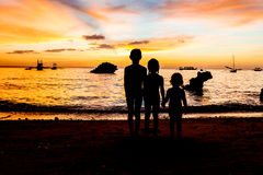 Kid silhouettes on sunset sea background Stock Image
