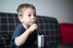 Kid sipping juice while watchnig tv Royalty Free Stock Photos
