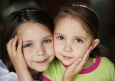 Kid sisters. Close up of cute young sisters holding each others faces in their hands. One with blue eyes and freckles, the other with brown eyes Royalty Free Stock Photography