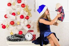 Kid sit near christmas tree hold teddy bear gift. Best gift ever. Excitement replaced with strong feeling satisfaction. Little girl santa hat satisfied royalty free stock photo