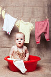 Kid sits in a basin Stock Image