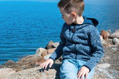 Kid sits on a rocks near sea at Finland. Young handsome boy and nature, scandinavian look Royalty Free Stock Images