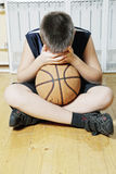 Kid sitting with basketball on floor Royalty Free Stock Photography