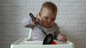 Kid is sitting behind the children`s table and examine silicone brush and ladle stock footage