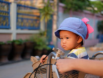 Kid is sitting on the bicycle basket in exercise with parent. Kid sitting on the bicycle basket in exercise with parent Royalty Free Stock Images