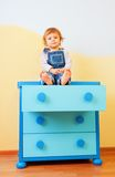 Kid sitting on the cabinet Stock Photo