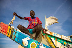 Kid sitting on a colored fisher boat in Senegal Stock Photo