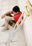 Kid sitting  with a crutches Royalty Free Stock Photos
