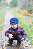 Kid sitting forest road fall season. Clothes Stock Photos