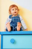 Kid sitting on furniture Stock Images