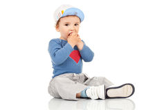 Kid sitting and holding his hands near the mouth Royalty Free Stock Photography