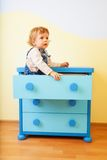 Kid sitting inside cabinet box Royalty Free Stock Photos