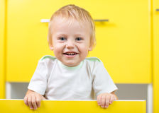 Kid sitting inside yellow opened kitchen box. Kid boy sitting inside yellow opened kitchen box Stock Photography