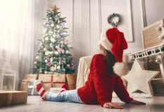 Kid sitting near Christmas tree indoors. Merry Christmas and Happy Holidays! Cheerful cute little child girl with present. Kid sitting near Christmas tree stock photos